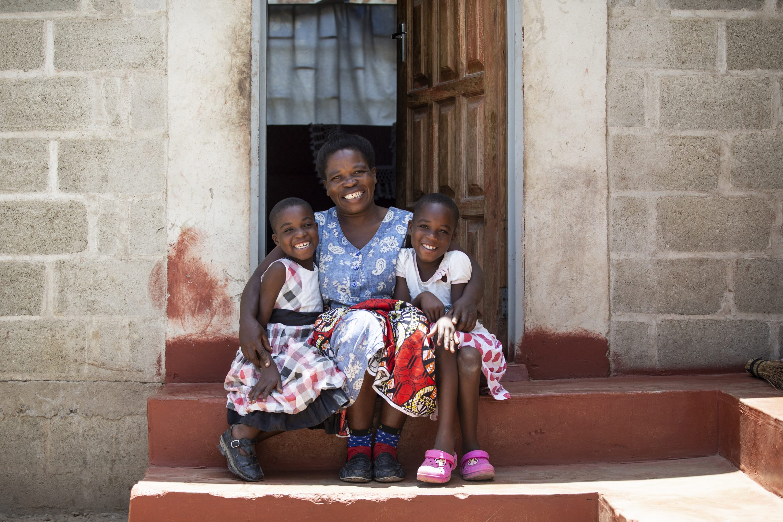 Kabwe, Zambia: Gertrude with her daughters, Naomi & Ruth outside their new Habitat home.